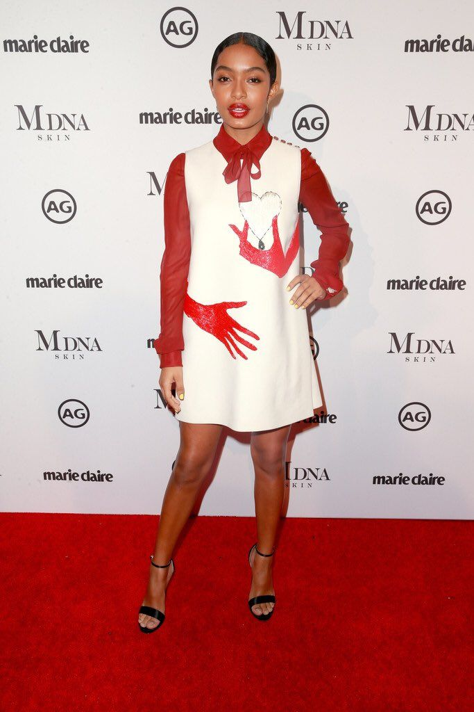 Yara Shahidi: Schiaparelli 'You Hold My Heart in Your Hand' tunic-dress in White Wool Embroidered with Red Glass Mini-tubes and a Blouse in Burgundy Silk Chiffon from the Fall 2017 Couture Collection.