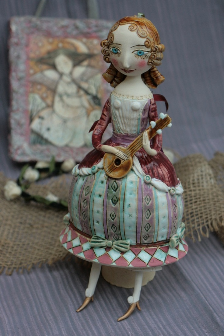 Young girl in purple dress playing mandolin. Ceramic bell, sculpture