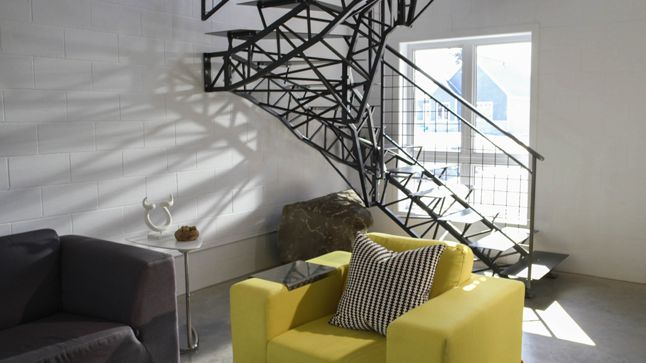 Le mélange des matières de cette pièce est très actuel. Juxtaposée à une fenêtre, la structure métallique de cette rampe fait réfléchir les rayons du soleil dans tous les sens.