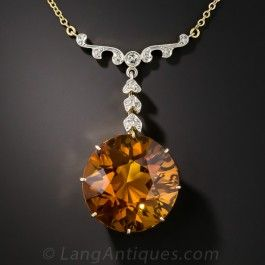 A big, beautiful, round brilliant golden citrine casts an enchanting amber colored glow in this uniquely lovely vintage necklace. The gorgeous gemstone is presented in an 18K stylized heart motif setting and suspends from a fanciful foliate motif pendant crafted in platinum over gold, and glinting with small round and rose-cut diamonds. Delicate and striking. The pendant measures 2 inches long by just over 1 inch wide, the chain is 16 inches.