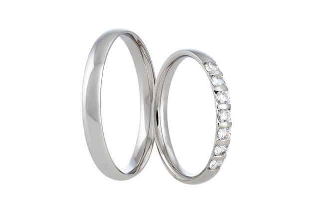 Elegantní pár snubních prstenů z bílého zlata v celolesklém provedení. Do dámského kroužku jsme vsadili sedm úchvatných kamenů
