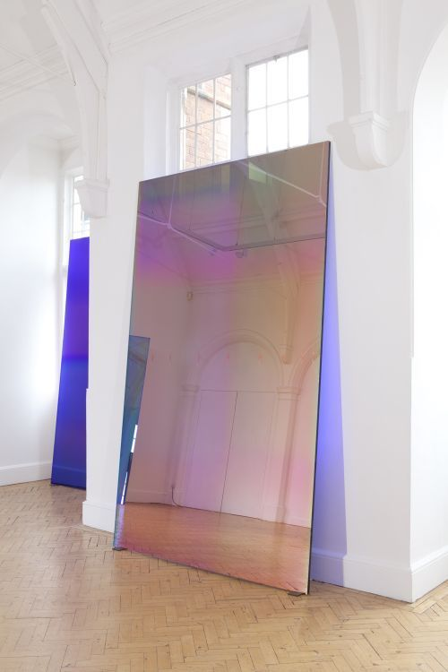 Raphael Hefti often works with material processes and in this work, he uses a glass coating process which is used for the production of 'museumglass'. By exaggerating and repeating this process, the large sheets of glass evolve with variable optical behaviour that will change with the ambient light in the gallery.