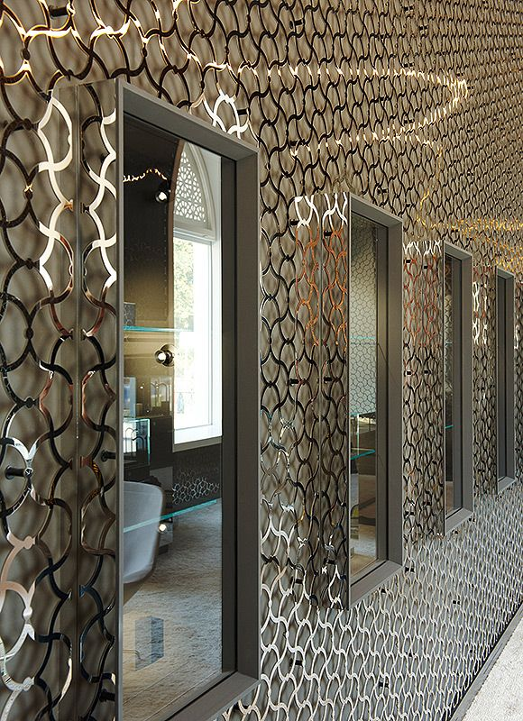 Dark walls overlaid with laser-cut  high polished stainless steel panels