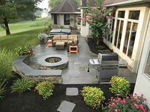 Work with professionals to create a landscaping layout that works for your family's needs. This patio, designed by Hively Landscapes, was designed with room for a fire pit, lounge area, hot tub and grill station—perfect for outdoor entertaining.