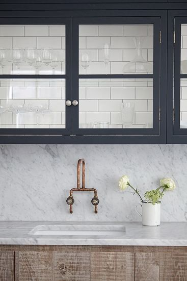 SGS Design favourite.  Industrial look, raw grey oak cupboards, glass-front wall cupboards, marble worktops and brass kitchen wall tap.