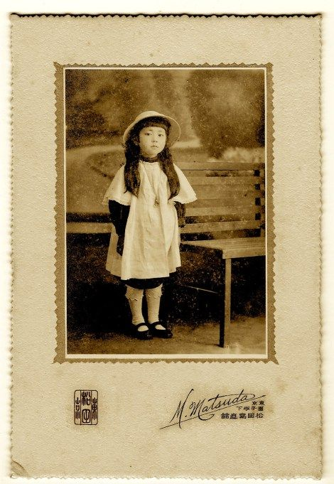 This vintage photograph compensates for its less than stellar condition by featuring a very cute five year-old girl. She looks adorable in her nice outfit as she displays her long hair under a pretty hat. The previous owner of this image stated that it dates to the Taisho period (1912-1926). It was also reported that the young girl in this photograph was five years of age at the time the image was taken. The photographer of this photographic portrait is M. Matsuda of Tokyo, Japan.