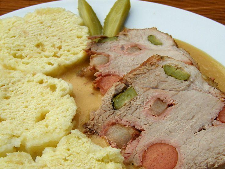 Maso prošpikujeme nakrájenými okurkami,částí slaniny a párkem. V kastrolu rozehřejeme trochu oleje a lžíci másla, přidáme kostičky zbylé slaniny...