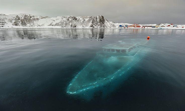 """Le yatch submergé, Antartique. Le Mar Sem Fim estun bateau fantôme, coulé près de """"Ardley Cove"""" en Antartique. Yatch brésilien dont l'équipage venait réaliser un documentaire, il fut prit dans une violente tempête de neige et abandonné par son équipage. La température de l'eau qui entoure le bateau gèle la coque et lui confère cette couleur d'un autre monde !"""