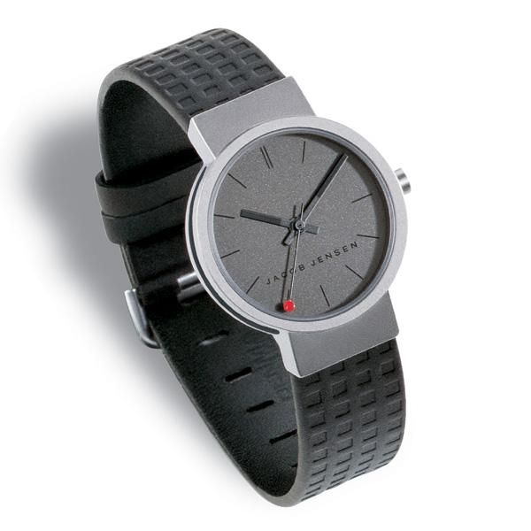 The clear series 421 watch by Jacob Jensen features a textured rubber band which sits comfortably on the wrist and has a minimal display that is typical of the Jacob Jensen design studio. Features: Charcoal face Glossy charcoal hands with matt black tips Black second hand with a red dot on the tip