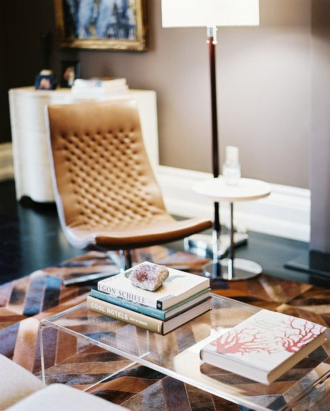 Living Room Photo - A transparent coffee table and a leather chair atop a geometric rug