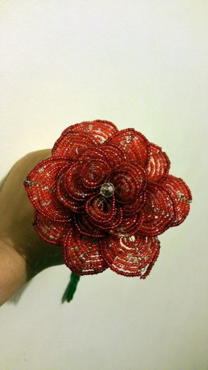 A large red french beaded flower with many pointed petals.