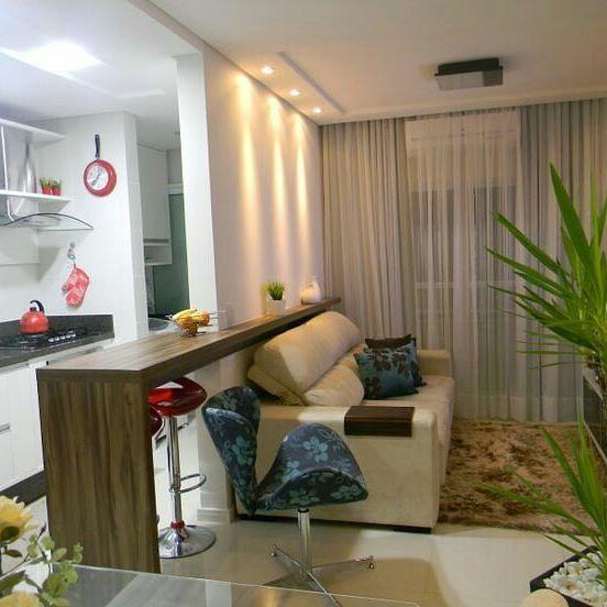 Bom dia! Sala pequena + cozinha americana integradas de forma harmoniosa. A bancada em madeira uniu o útil ao agradável, pois dividiu os espaços entre os dois ambientes e ainda criou um local para refeições rápidas. Atenção para essa dica de iluminação: as luzes quentes (amarelas) são mais indicadas para salas e quartos, enquanto as luzes frias (brancas) são mais utilizadas em cozinhas e banheiros. Pinterest #blogumeuminiape #meuminiape #apartamentospequenos #inspiração #sala…