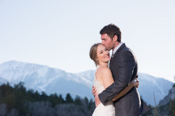 Vibrant Photo at Sunset with Mountain background.  Photos where the Couple pops. Kissing Cheek