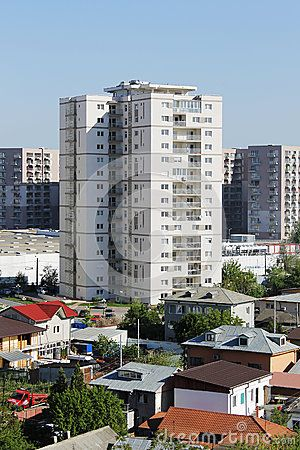 14-storey block near other big buildings and houses in residential area from Bucharest, Romania.