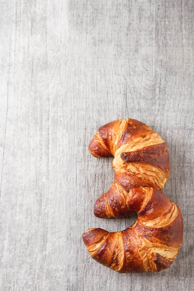 French food for breakfast. Fresh baked croissants. Light wood background. Top…