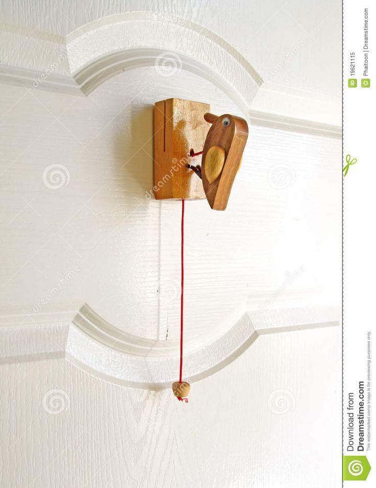 animal door knockers | Wooden bird door knocker on the white door.