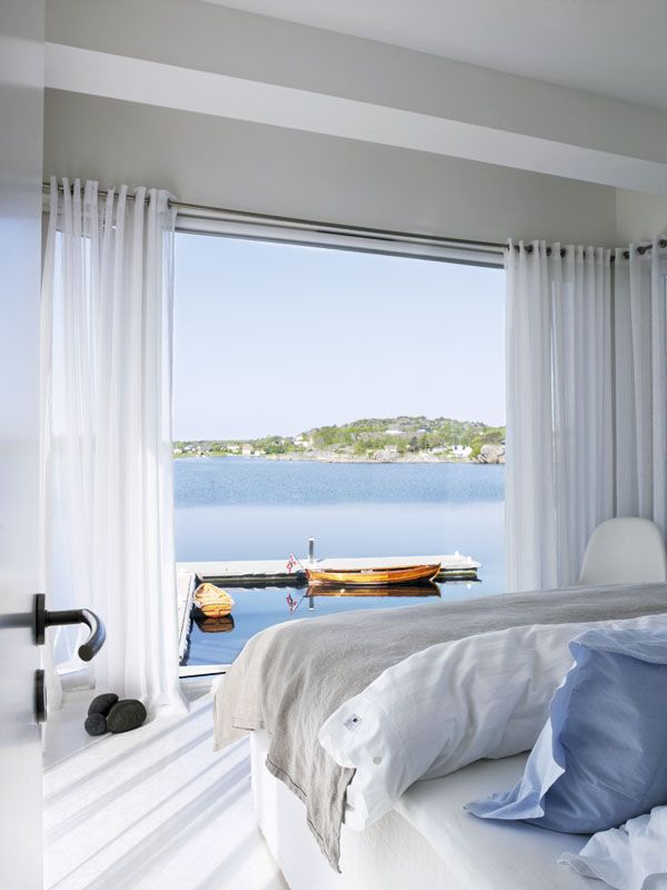 The soft voile curtains and delicate blue bedding creates the perfect decor for the stunning beach backdrop. #interiordesign #bedrooms