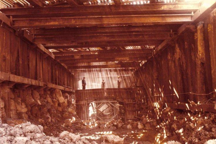 Building the Melbourne Underground Rail Loop. Three men stand in a large steel frame, with sludgy mud below