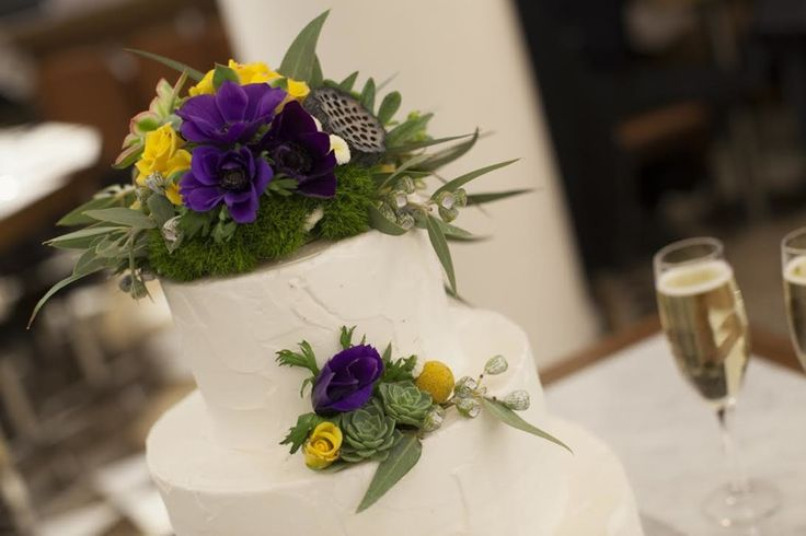 Candida Purezza - Three-tiered cake finished in buttercream topped with yellow and purple roses