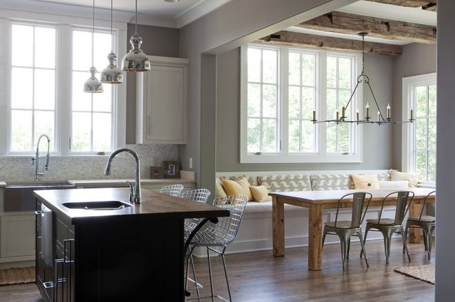 The knotty wood table, overhead beams and traditional candle chandelier add farmhouse charm to this contemporary kitchen.