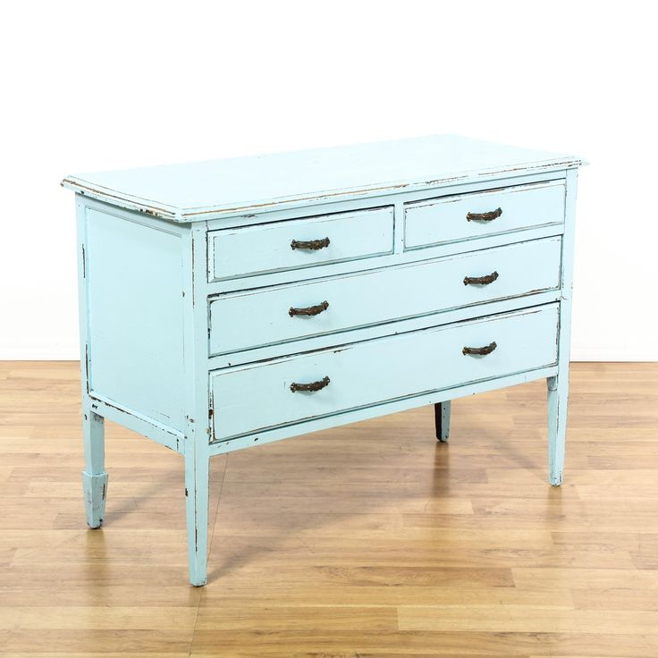 This shabby chic chest of drawers is featured in a solid wood with a distressed light blue paint finish. This short dresser has 4 drawers, a raised base and tapered legs. Perfect as a buffet sideboard! #shabbychic #dressers #shortdresser #sandiegovintage #vintagefurniture
