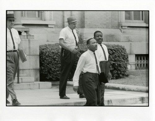July 10, 1962: Martin Luther King Jr. and Ralph David Abernathy were convicted of charges stemming from his 1961 attempt to desegregate government buildings in Albany, Georgia. The judge sentenced them to a $178 fine or 45 days in jail. Dr. Martin Luther King, Jr., and Reverend Ralph Abernathy are escorted from the courthouse back to jail in Albany. [Memories of the Southern Civil Rights Movement] 1962. Danny Lyon.