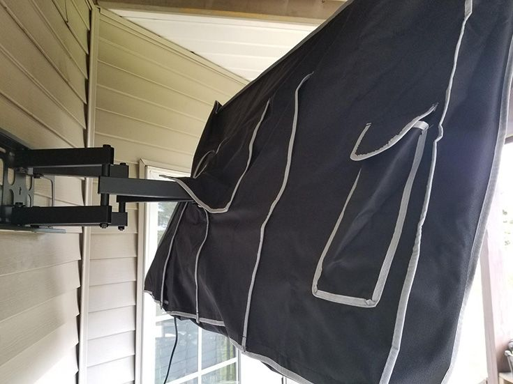 Outdoor Tv Mounted On Articulating Wall Mount And Covered With