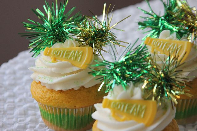 Green, yellow, white vanilla cupcakes with vanilla buttercream. Topped with chocolate megaphones decorated with edible glitter. Pom poms made from garland and attached to toothpicks.