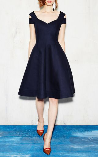 This **Paule Ka** dress features a fitted bodice, a pleated full A-line skirt, and a cold styled shoulder.