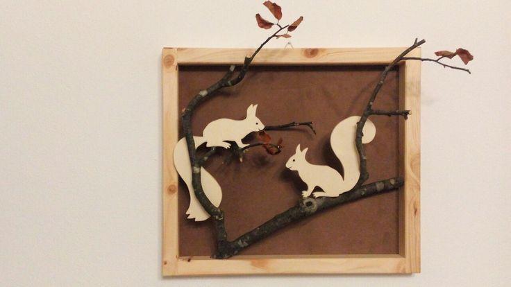 Die Eichhörnchen aus Speerholz ausschneiden. Der Rahmen wurde aus Holzleisten in die gewünschte Größe zurechtgeschnitten und mit Holzleim zusammengeklebt. Als Rückwand habe ich einen braunen Stoff verwendet. Einen passenden Ast suchen und alles mit Heißklebe befestigen. Aufhängen.