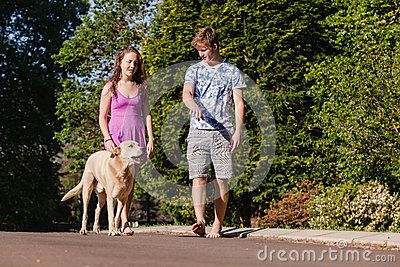 Teen girl boy relaxing summers day walking talking with dog.