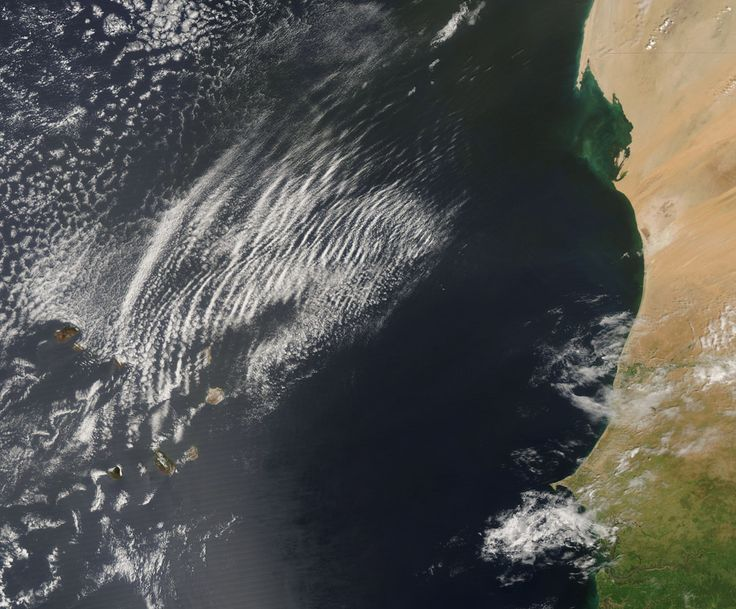 Known as wave clouds, these long, semicircular clouds were created by cool dry air coming from over Africa interacting with warm, humid air over the Atlantic Ocean. This image was captured by Aqua on Oct. 9, 2007.
