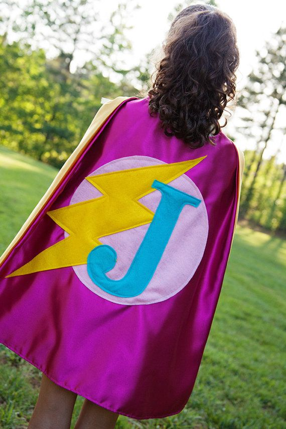 """Our high quality custom superhero cape ships in 2-3 business days.  This listing is for the exact color combinations shown above, with your choice of initial (or number if you prefer). If purchased you will receive:  Pink satin cape (yellow lining), light pink felt circle, yellow felt lightning bolt, turquoise felt letter  If you would like the felt embellishments (shapes/initial) to be in different colors please send me a convo.  Our satin capes are HANDMADE MADE IN THE USA and measure 22""""…"""