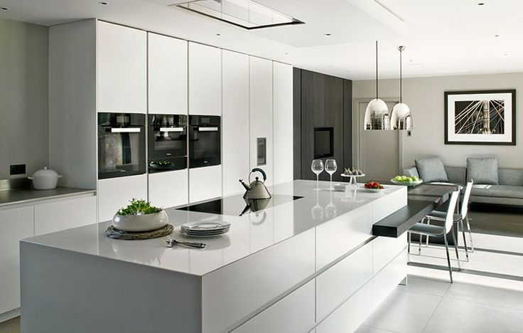 Modern kitchen design with large island and adjoined dining table. Handleless kitchen cabinets in Signal White Matt Lacquer with Dark Stained Oak contrast. Worktops in stainless Steel and Compac Absolute Blanc Composite Stone.