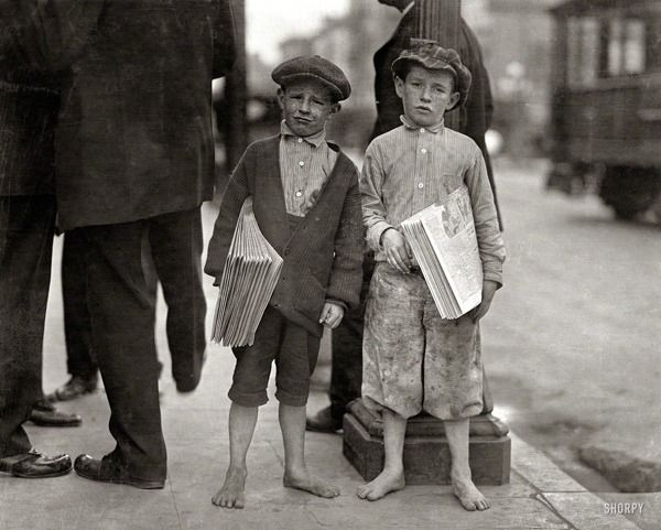 """May 1915. """"Nine-year-old newsie and his 7-year-old brother 'Red.' Tough specimen of Los Angeles newsboys."""" Photo by Lewis Wickes Hine."""