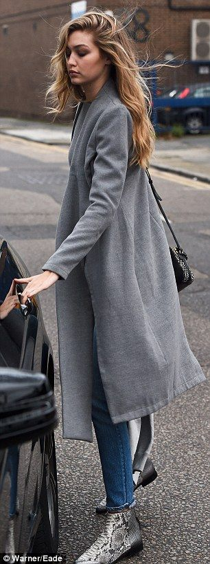 Picture perfect:The catwalk queen kept the chilly British weather at bay with a matching gunmetal coat and completed her look with a pair of stylish crocodile-print boots