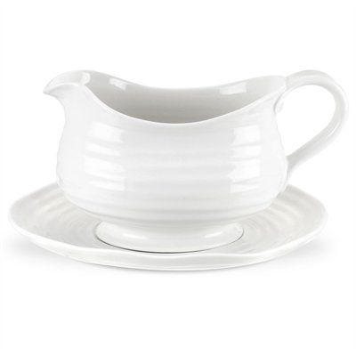 Beautiful yet practical, Sophie Conran's porcelain gravy boat and stand has a graceful handle and spout for an easy pour. Its uplifting tactile design has a fresh contemporary feel that brings joy to any occasion, while it's white glaze works in any setting. 24-oz./591 ml capacity. Dishwasher-, microwave-, oven-, and freezer-safe. By Sophie Conran for Portmeiron.