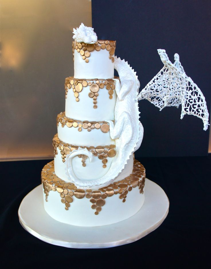White chocolate dragon wedding cake with gold falling circles and edible lace wings!
