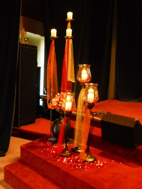 The candles all dressed for Pentecost: sparkly tulle, orange mylar shred, and fiery-colored paper flowers.