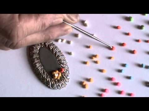 Video: Polymer clay embroidered flower pendant - the tiny balls of clay are shaped into flowers and leaves with clever use of a crochet hook.  #Polymer #Clay #Tutorials