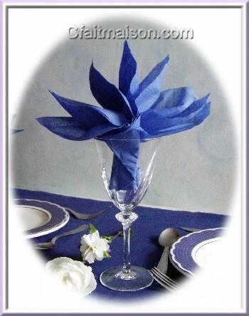 Serviette pliée en forme de strelitzia, dans un verre.