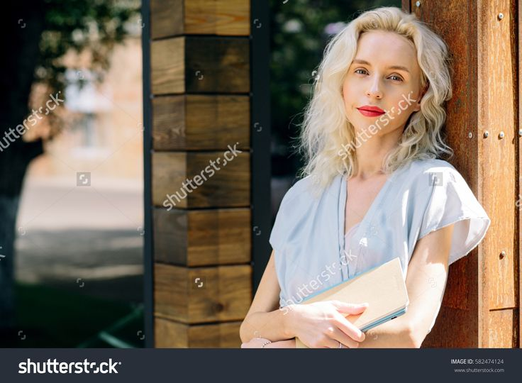 Portrait of young beautiful blonde woman in Asian style blue trendy dress posing outside in the city streets. Smiling girl standing next to wooden building. Close up. Fashion concept. Natural beauty
