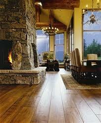 Huge stone fireplace in the middle, open floor plan, wood floors, chandelier