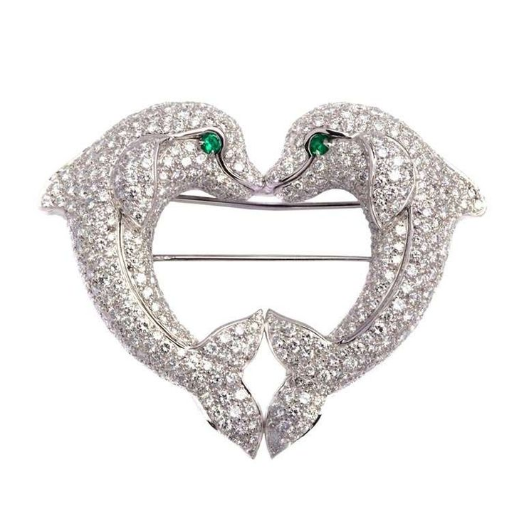 Cartier A Heart-shaped Dolphins Brooch. An elegant brooch manufactured by Cartier during the 1980s, representing a heart shape entailed by the encounter of two loveable dolphins. The item presents approximately 10cts of very fine quality brilliant cut diamonds and two emeralds (eyes) on a platinum mounting.