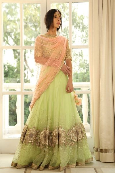 Mint green net lehenga with bronze embroidery with a scalloped egde pink net dupatta and sequinned blouse