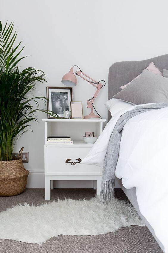 lampe de chevet rose poudrée, table de chevet repeinte, tapis douillet et plante verte