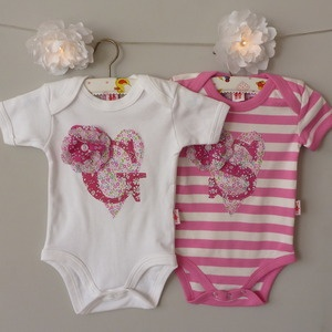 £20.00 Hand Made Personalied Letter Bodysuit, with applique Liberty Letter , Heart & Corsage, available in Bubble Gum Pink Fair Trade Stripe or White.