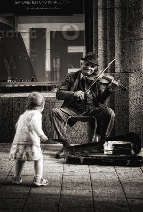 Insouciant child dancing to the old man's music . Young and old alike enjoying music together, how nice.