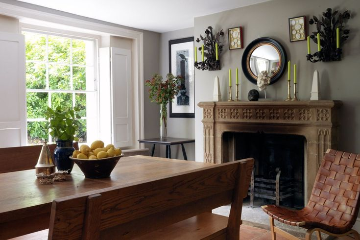 """This dining room in North London with its wonderful Victorian windows, is simply furnished with an oak table and benches from [link url=""""http://www.chestofdrawers.co.uk/""""]Chest of Drawers[/link] in Islington. Attention focuses on the Mise-en-scène on the chimney breast, created by its owner Intaglio boxes are flanked by a covetable pair of sconces set with lime-green candles"""
