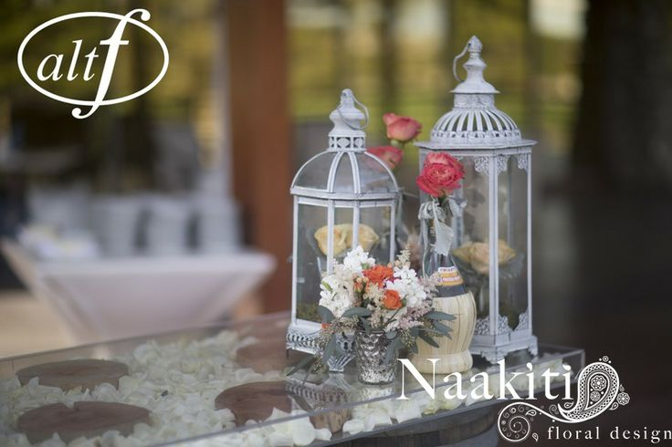 Cocktail hour: As a table, we used out plexi glass top over our two wine barrels w/ lanterns and bud vases. The inside is filled with rose petals. #cocktail #wedding #roses #altf #naakitifloral